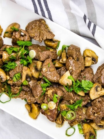 keto Garlic steak & mushrooms on a rectangular platter