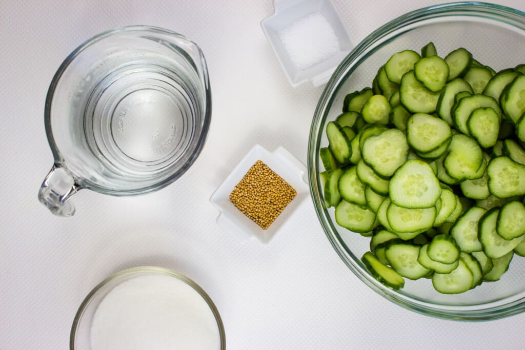 sliced cucumbers and other ingredients to make keto pickles