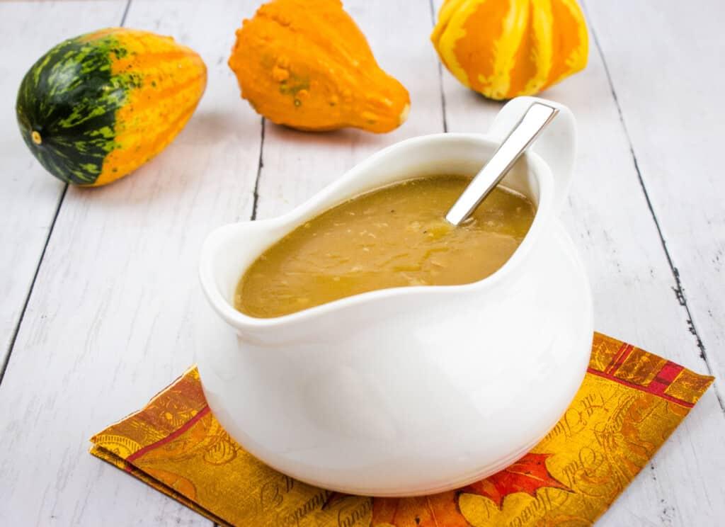 keto turkey gravy in a gravy boat with gourds in background