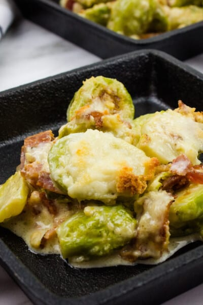keto parmesan brussels sprouts with bacon in a black cast iron serving dish