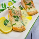 salmon with lemon-herb butter sauce on a platter
