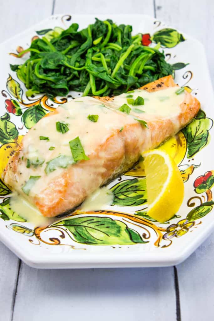 keto salmon with lemon herb butter sauce and spinach on a plate