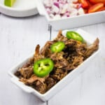 keto beef barbacoa recipe with tortillas in background