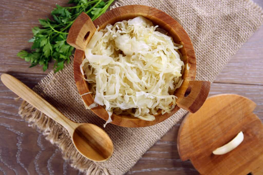 sauerkraut in a wood serving barrel with spoon nearby