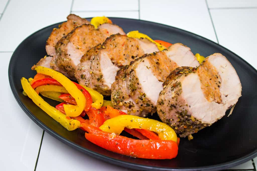 sausage stuffed pork tenderloin with peppers on a plate