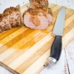 sliced sausage stuffed pork tenderloin on a cutting board