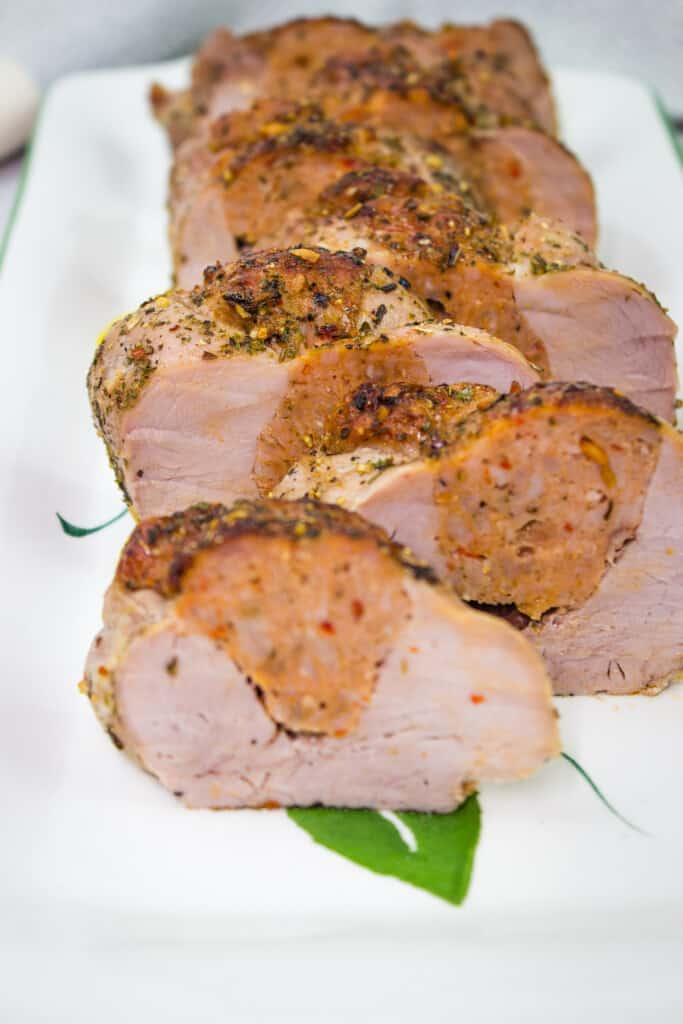 sausage stuffed pork tenderloin on a platter