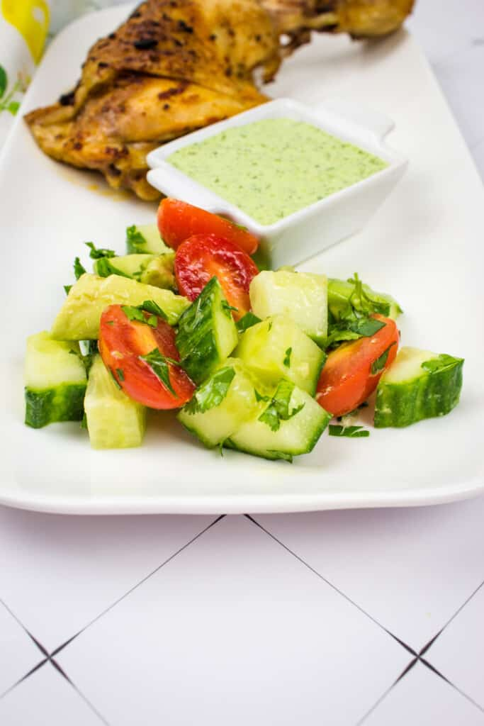 cucumber, tomato, avocado salad on a serving plate with peruvian chicken and green sauce in the background