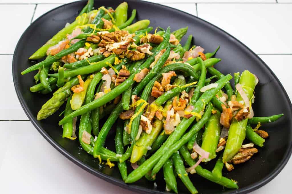 keto green beans & asparagus with lemon & Pecans on a black serving platter