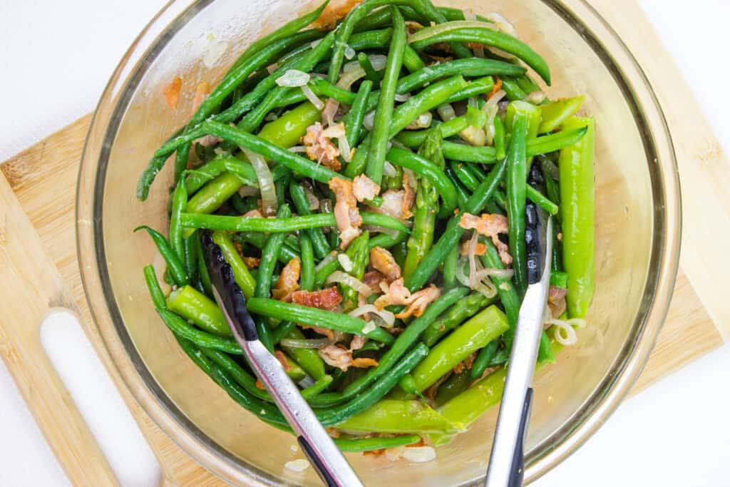Beans, asparagus and bacon shallot mixture tossed in a bowl.