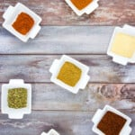 measured spices in small white dishes on a wooden board to make keto chili spice mix