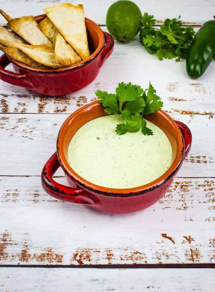 keto creamy jalapeno dip in a rustic bowl with tortilla chips in the background