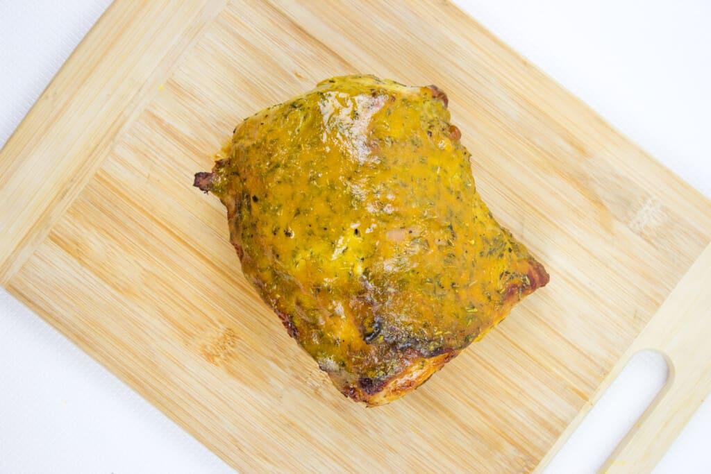Brown sugar mustard glaze pork roast resting on a cutting board.