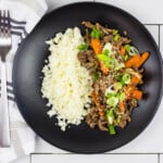 keto korean beef bowl on a black plate with cauliflower rice