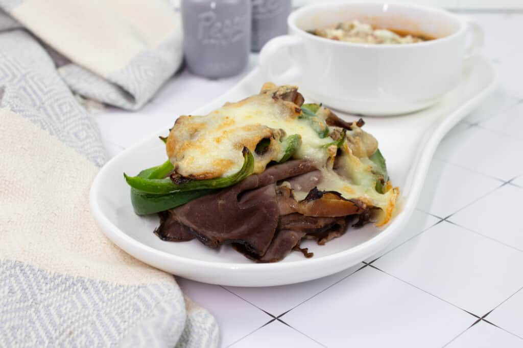 keto philly cheesesteak stacks on a plate with soup in the background