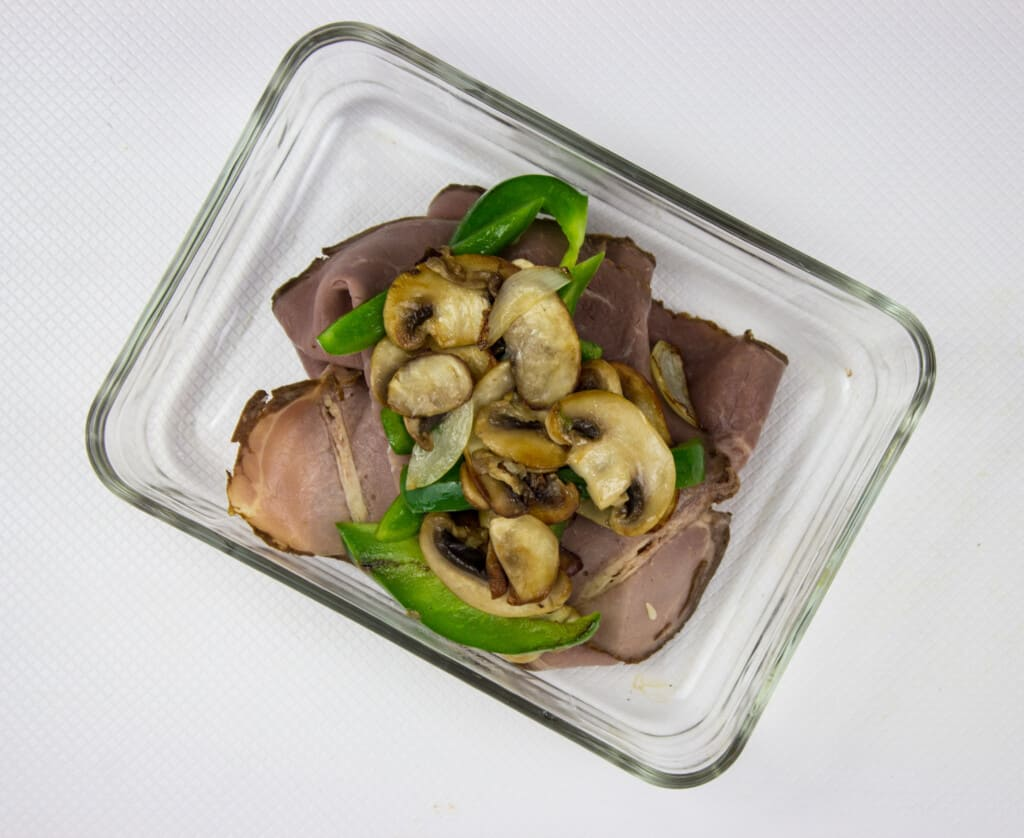 sauteed onions, mushrooms and peppers on top of sliced beef in a baking dish