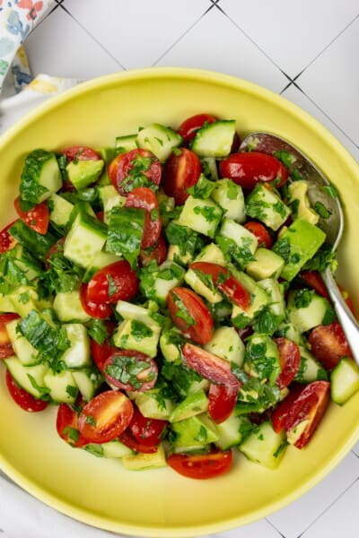 cucumber, tomato, avocado salad in a bowl with avocados and a napkin in teh background
