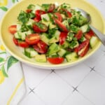 cucumber, tomato, avocado salad in a yellow serving dish
