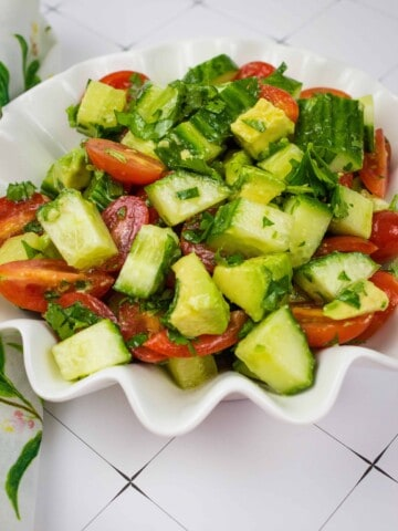 cucumber, tomato, avocado salad in a scalloped serving bowl