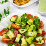 cucumber, tomato, avocado salad with chicken in teh background