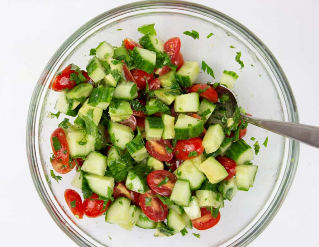 chopped veggies to make cucumber, tomato, avocado salad topped with teh dressing