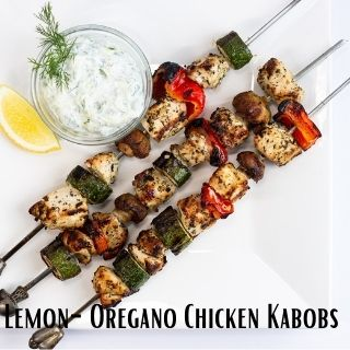 lemon oregano chicken skewers on a white plate with a side of tzatziki
