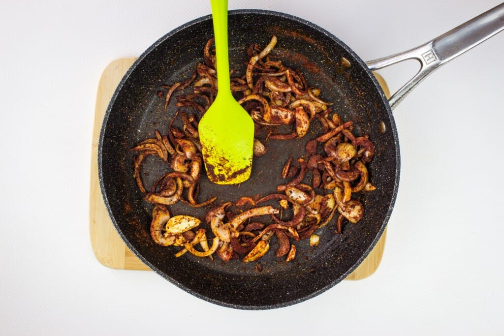 adding the spices to the onions in a skillet