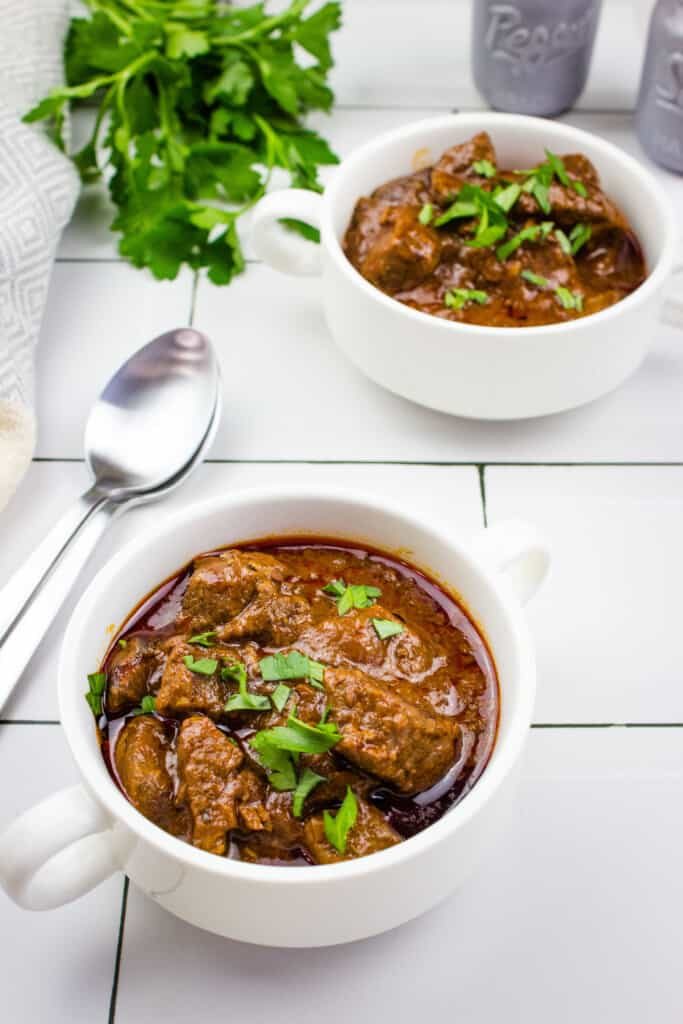 hungarian keto goulash in white serving bowls with parsley and spoons nearby