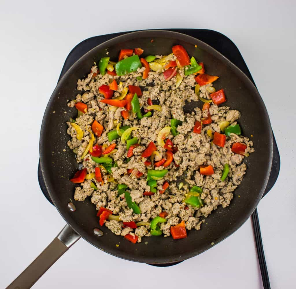 a skillet with ground turkey and red and green peppers in it. Enjoy your keto ground turkey and peppers meal!