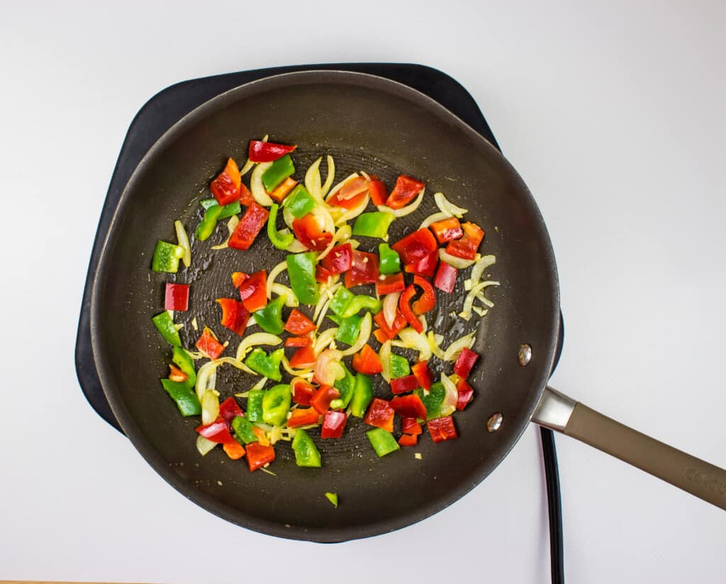 adding the red and green peppers to the sauteed onion to make ground turkey and peppers.