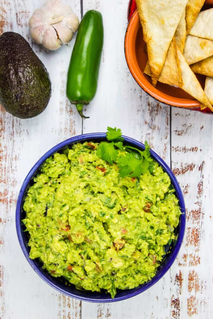 easy keto guacamole on a table with chips and veggies in the background.