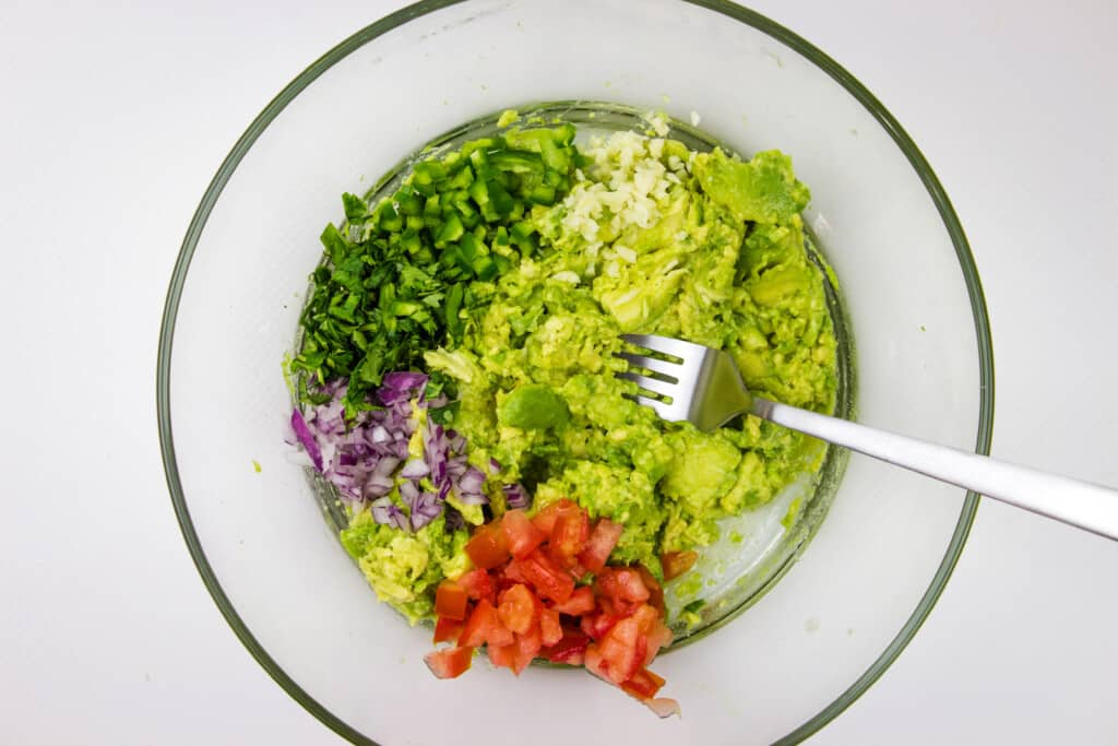 all ingredients in a bowl with a fork for mashing the avocado and stirring the ingredients