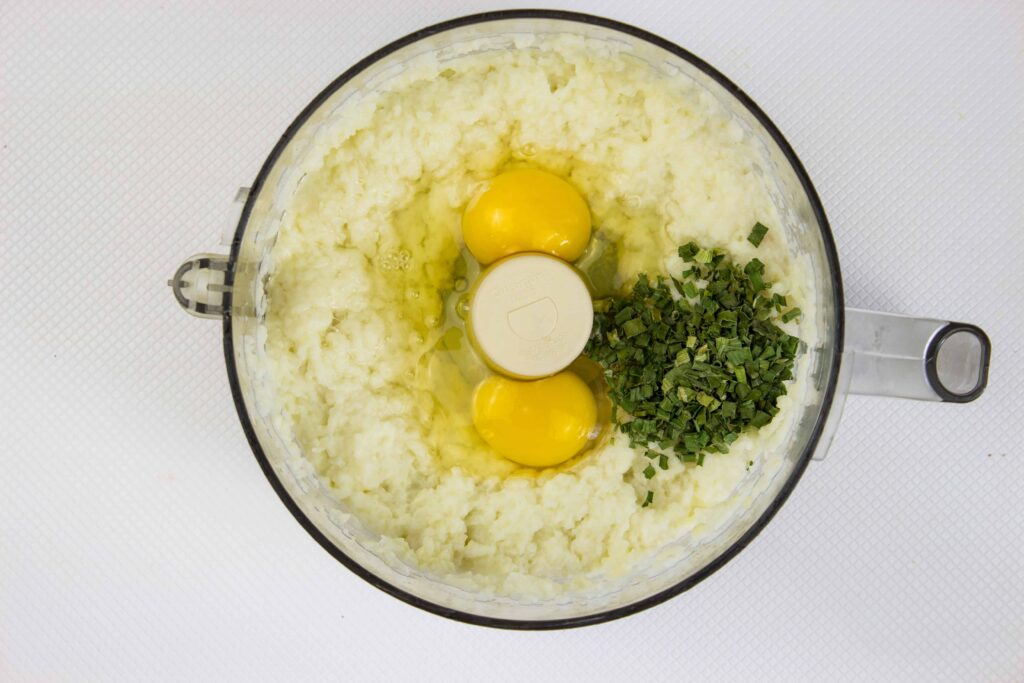 mixing the eggs and chives with the whipped cauliflower in a food processor