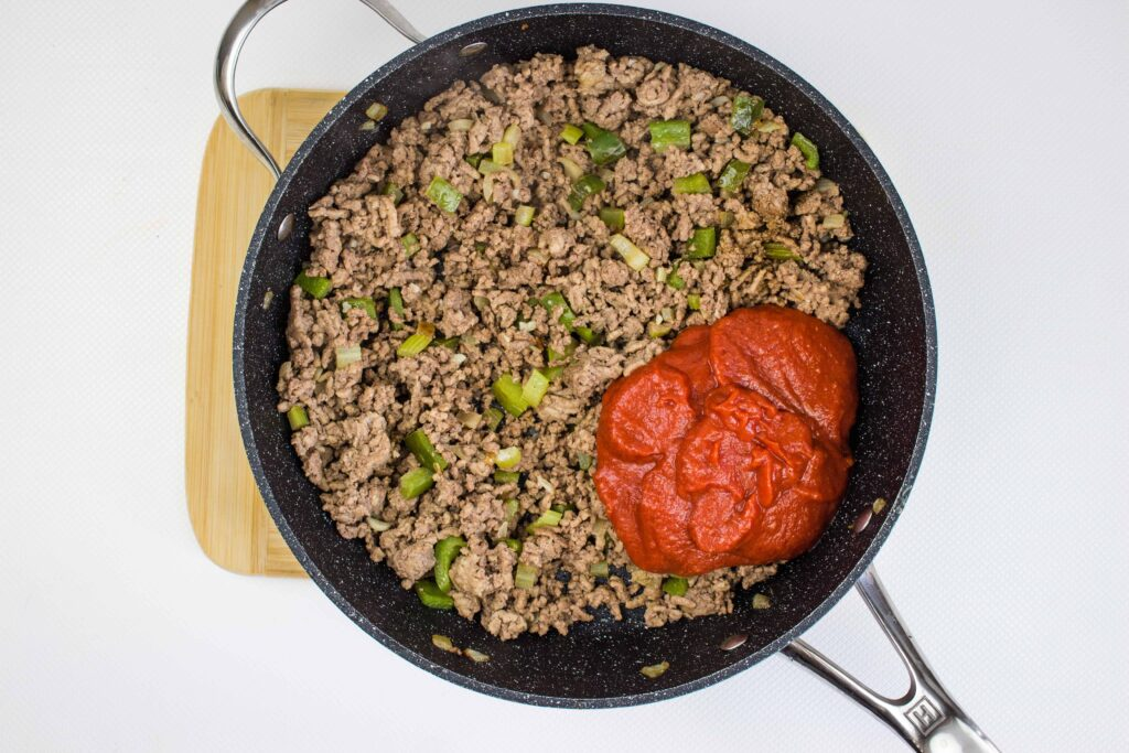 adding the tomato to the browned beef and veggie mixture in teh skillet