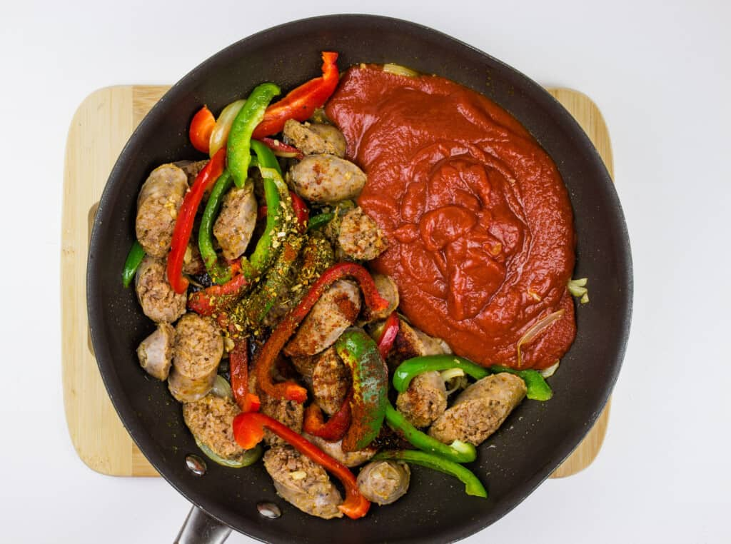 adding tomato sauce and spices to the skillet and heating it through