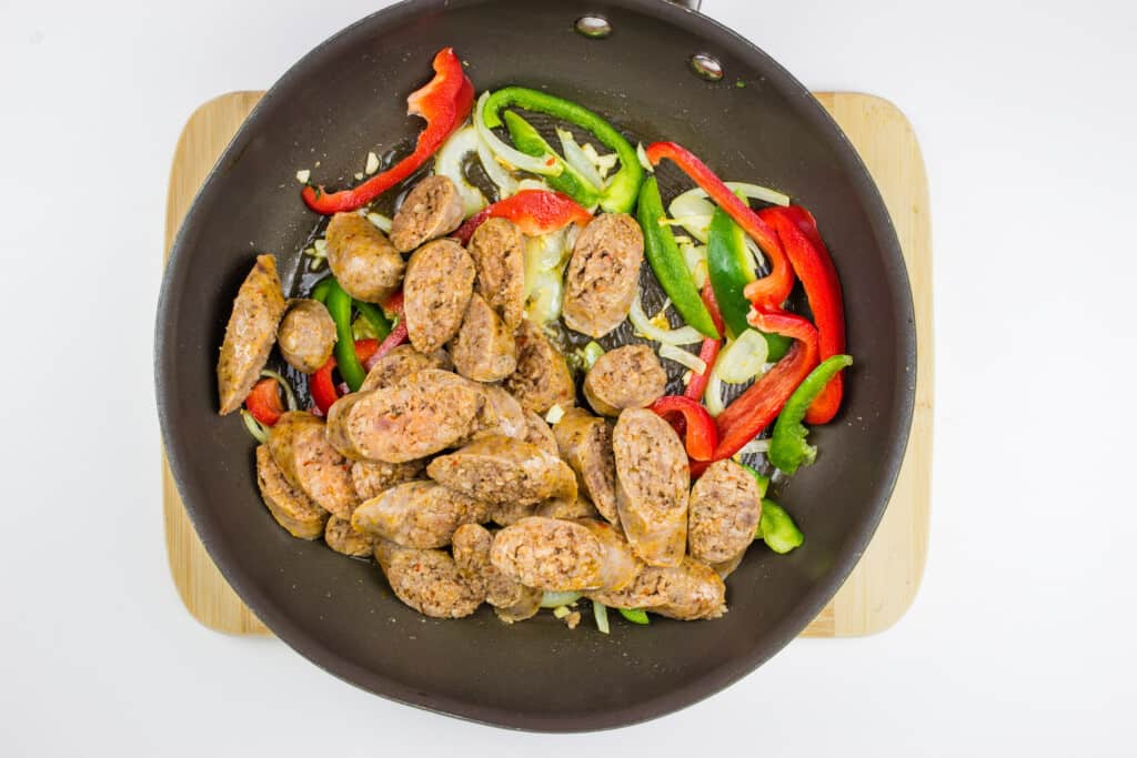 adding the sausage to the vegetables in the skillet