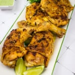 Oven-roasted Peruvian chicken on a platter with Peruvian chicken sauce in the background.