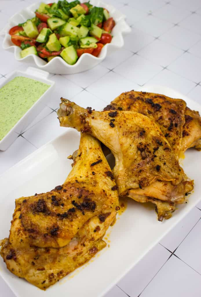 oven roasted peruvian chicken with a tomato, cucumber and avocado salad in the background