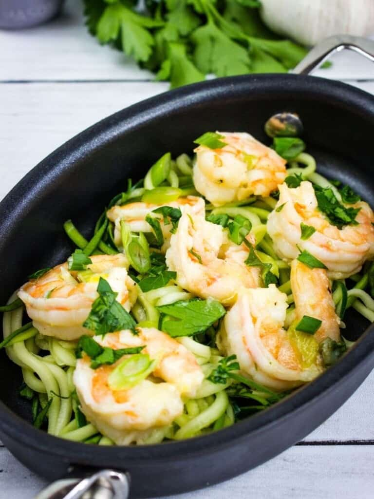 shrimp scampi in an oval serving dish with zucchini noodles