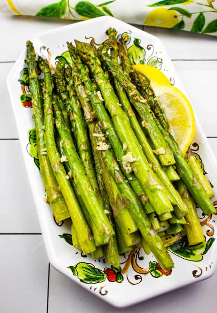 air fryer asparagus on a platter with a lemon wedge