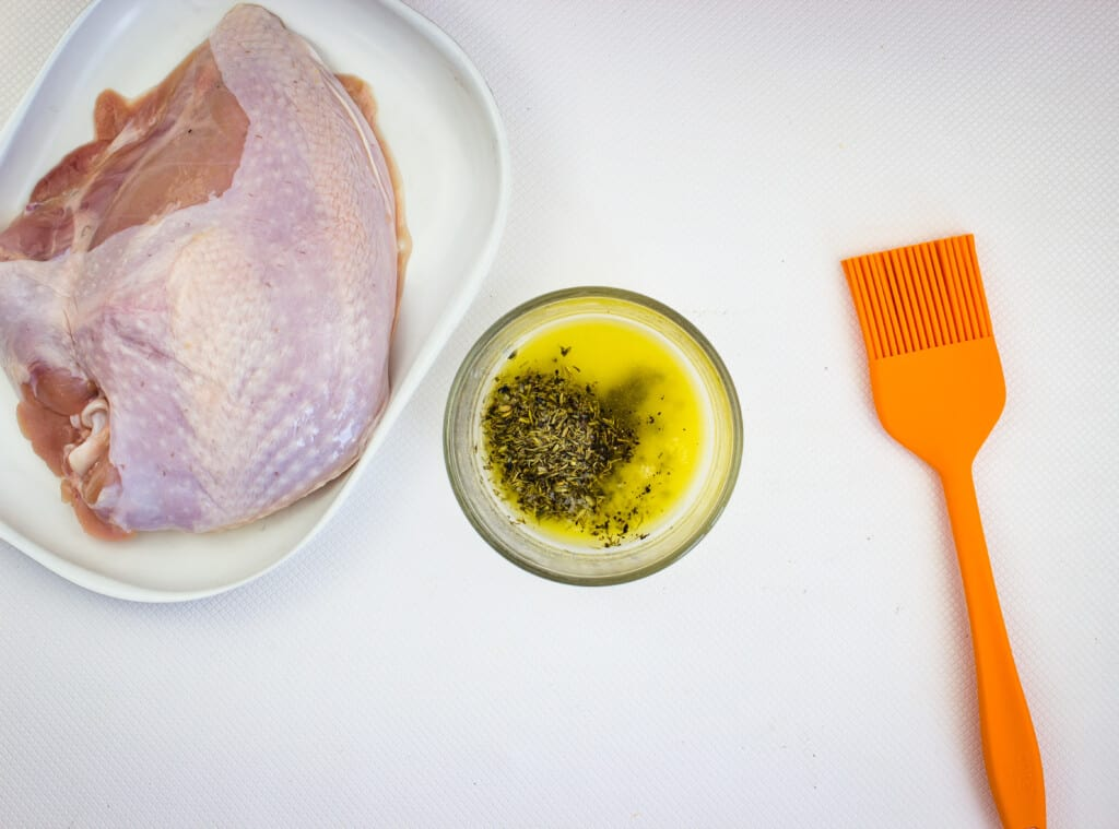 turkey breast with a bowl of herbed butter and a silicone brush to the side