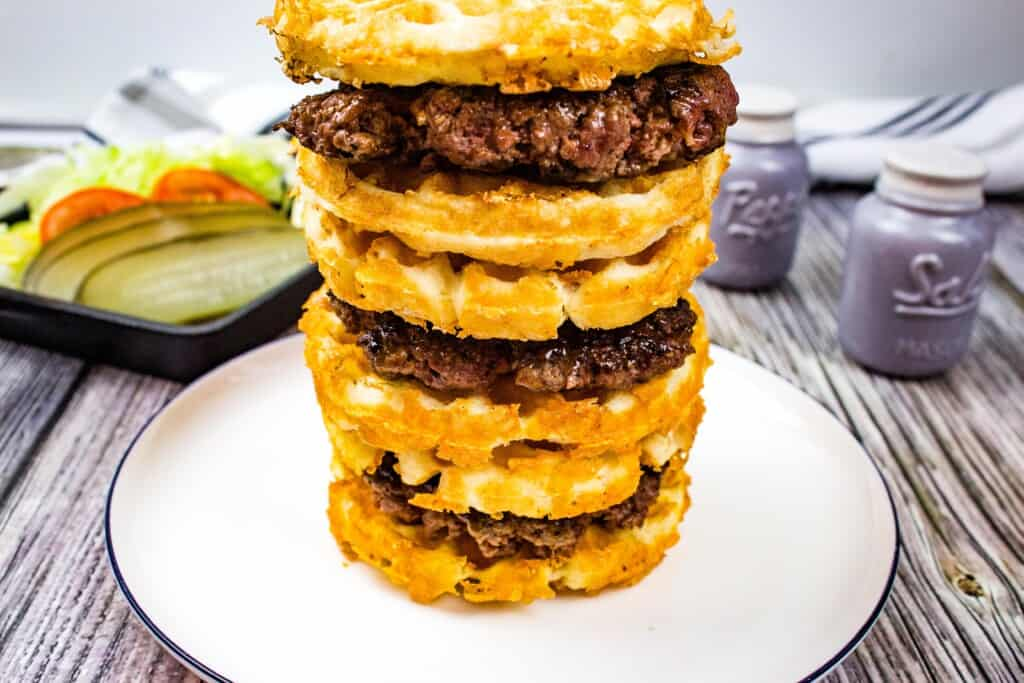 a stack of three keto butter burgers with condiments in the background