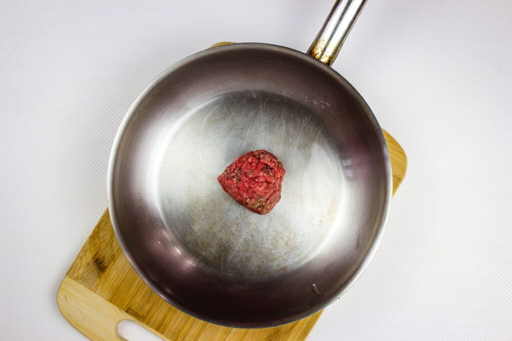 a heated skillet with a portion of ground beef in it