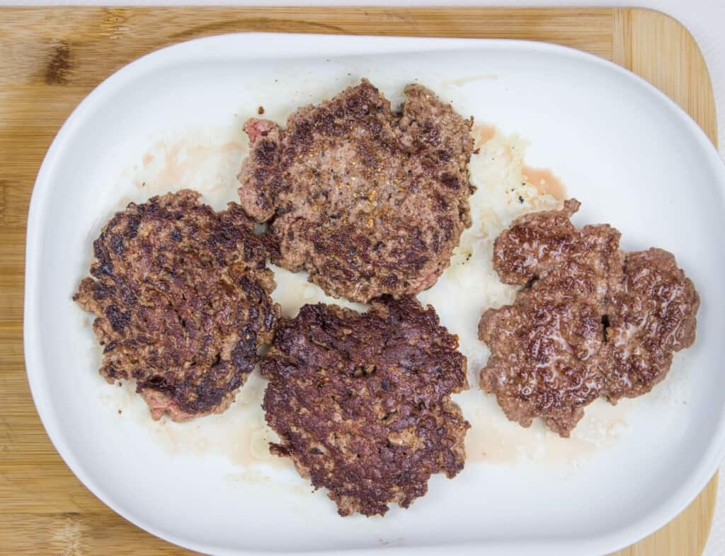 four portions of seared keto butter burgers ready for chaffle buns