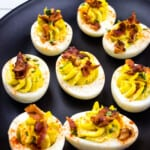 keto deviled eggs with bacon on a black platter