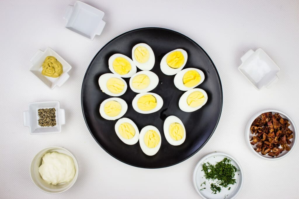 perfectly boiled eggs and prepped ingredients to make keto deviled eggs with bacon
