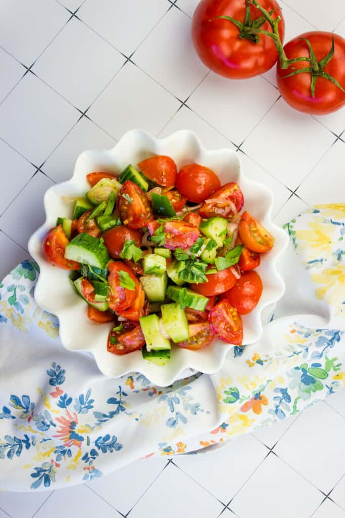 keto cucumber tomato salad in a white serving bowl