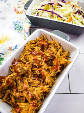 keto pulled pork in the instant pot in a serving dish with coleslaw in the background