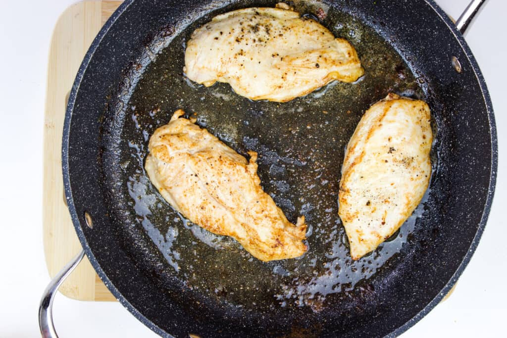 chicken breasts browning in a skillet.