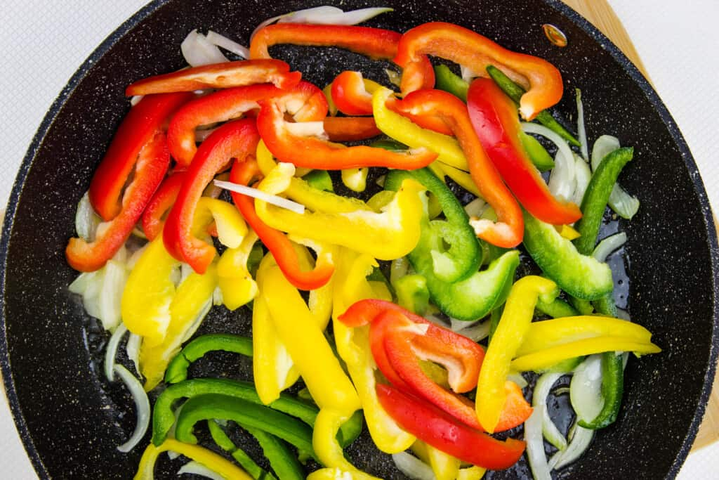 Add the peppers and cook until tender crisp